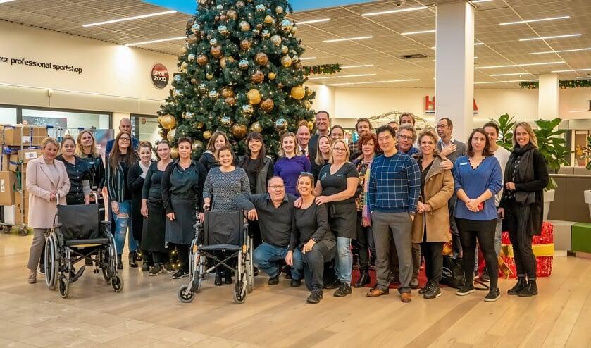 Ook de winkeliers staan achter het plan voor een rolstoeluitleen in Winkelhof. Een groot aantal van hen ging vorige week met Annelies Hoedt (geheel links) en Mariette Meulman (achter rechter rolstoel) op de foto als teken van steun. De beoogde rolstoelen zien er overigens niet zo uit als die op de foto.   Foto: J.P. Kranenburg