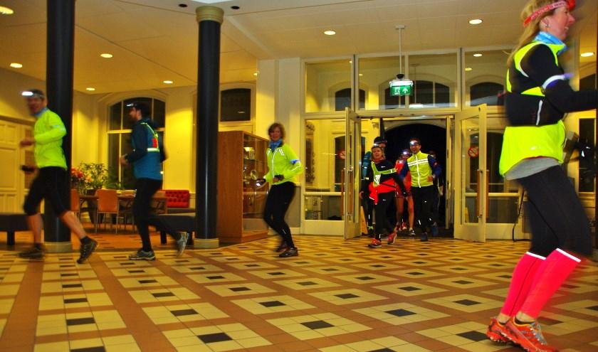 Deelnemers aan de eerste Oegstgeester nighttrail rennen door het gemeentehuis. | Foto Willemien Timmers