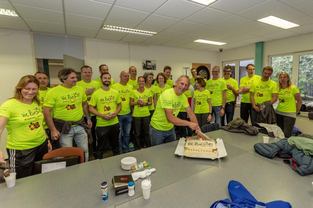 Teamlid Ad van Nieuwland was jarig op de dag van vertrek en sneed een taart aan.   Foto Wil van Elk Foto: Wil van Elk © uitgeverij Verhagen