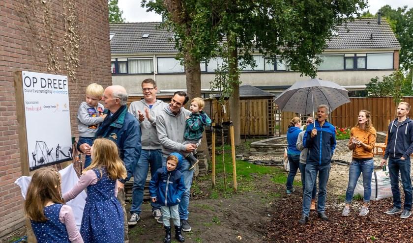 Wethouder Gardeniers opent de speelplaats, samen met enkele buurtkindren. Naast Gardeniers applaudisseert voorzitter Frank Versteegen van Op Dreef.