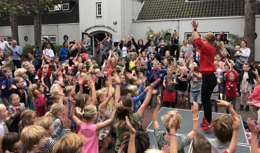 Kirsten Remmers van De Rode Sneakerz leert de kinderen van de Koningin Julianaschool een dansje.