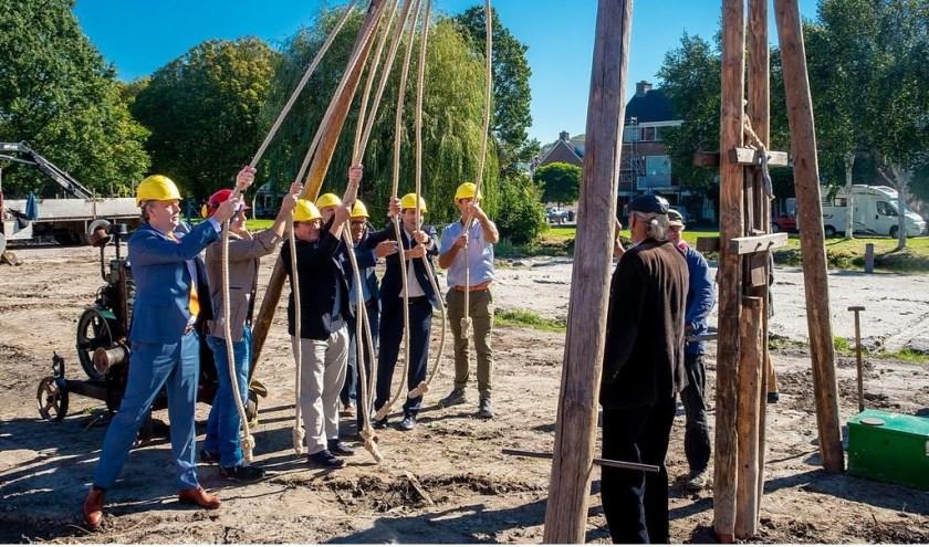Vertegenwoordigers van de gemeente, Rijnhart Wonen, aannemer Meerburg en architectenbureau ONIX staan klaar om de symbolische eerste paal te slaan.