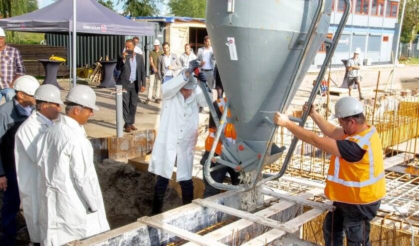 De Leiderdorpse wethouder Willem Joosten opent de kubel waardoor het beton in de bekisting voor de fundering kan stromen.