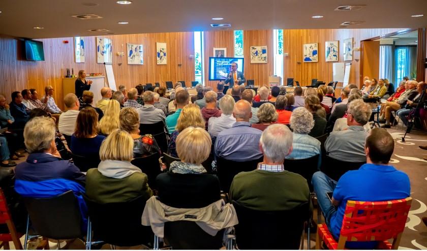 Wethouder Willem Joosten spreekt de eerste groep van ruim 150 bewoners toe. Links staat Maya van der Steenhoven van het programmabureau Warmte Koude Zuid-Holland.