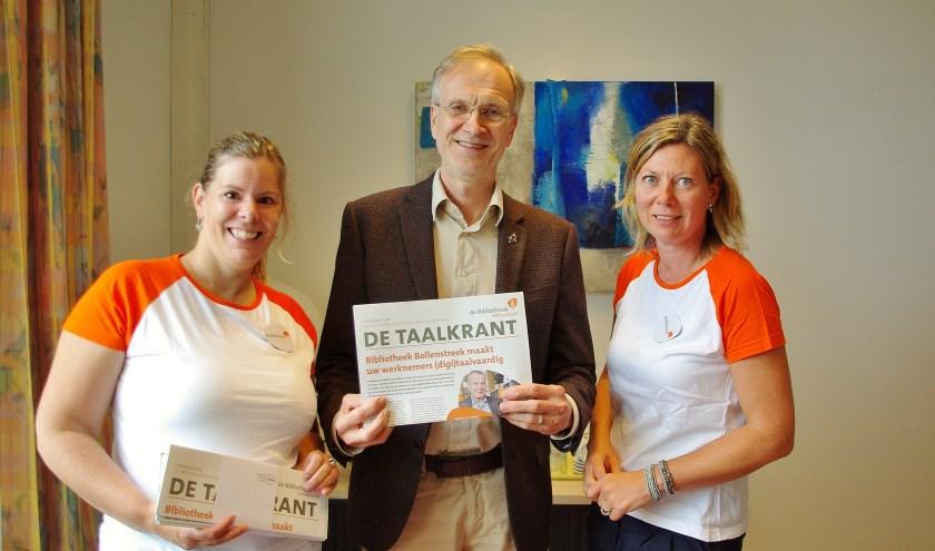 Eline de Visser (Projectleider Taalhuis) en Dionne Dinkhuijsen (programmamanager van de Bibliotheek Bollenstreek) bieden de  Taalkrant aan aan wethouder Jan Nieuwenhuis. | Foto Willemien Timmers