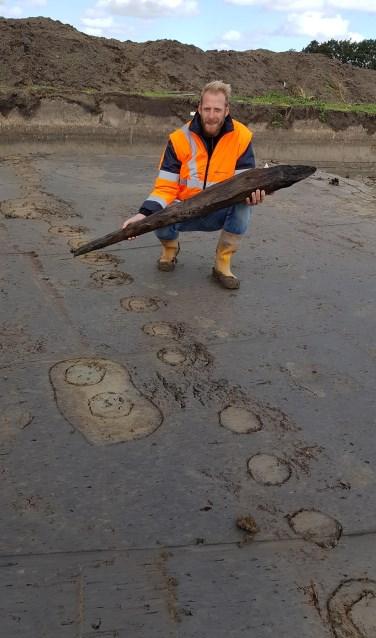 Archeoloog Jeroen Loopik met een stuk houten paal van de Romeinse weg