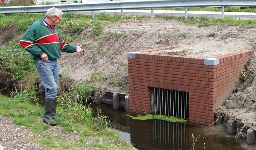Jan de Ridder wijst de oorzaak van de wateroverlast aan. Deze duiker zou 30 cm. moeten zakken. | Foto: Wim Siemerink