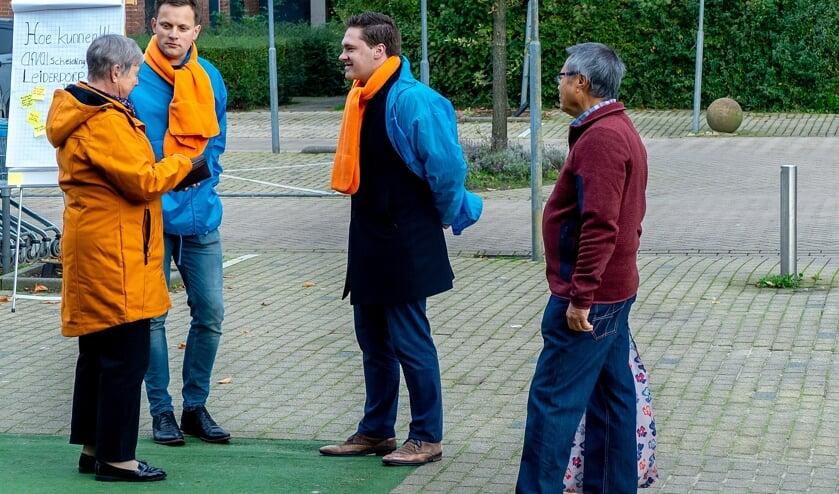 Geert Schipaanboord en Leander Tramper van CU-SGP-fractie (met blauwe jassen) in gesprek met Leiderdorpers. | Foto: J.P. Kranenburg