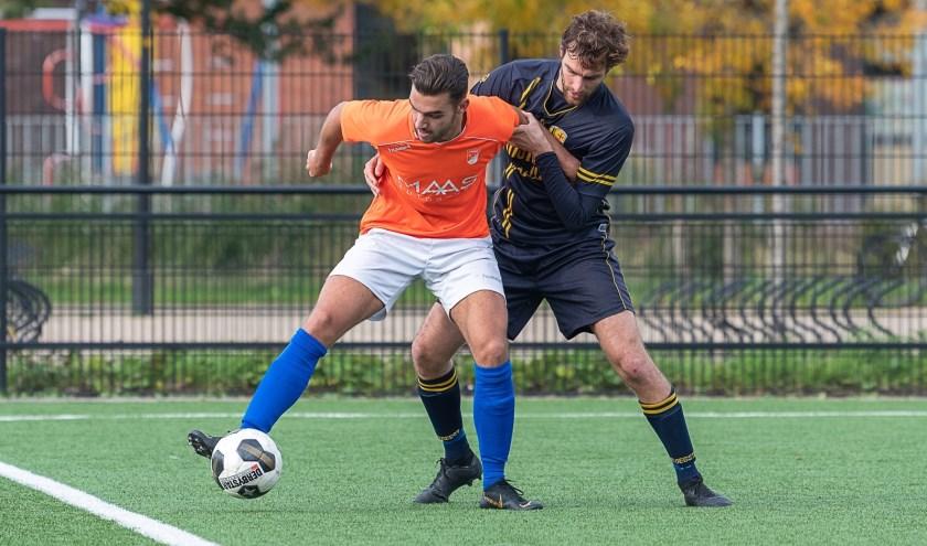 Ruben Groeneveld, verdediger van FC Oegstgeest, heeft zijn handen vol aan SV Nieuwkoop.