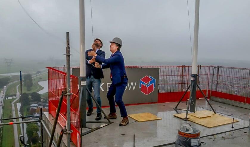 Bernlef de Vries van Vink Bouw (links) en wethouder Willem Joosten hijsen de vlag; het hoogste punt van de torenflat is bereikt.
