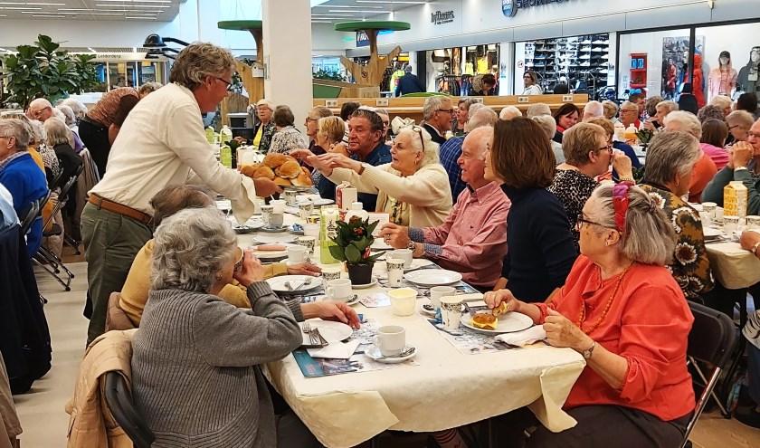 Marten Brederode deelt broodjes uit aan een van de lange tafels.