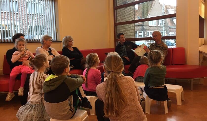 Ed Hoogkamer (met boek) leest voor, terwijl naast hem Paul Zwetsloot, samen met de kinderen, toeluistert.