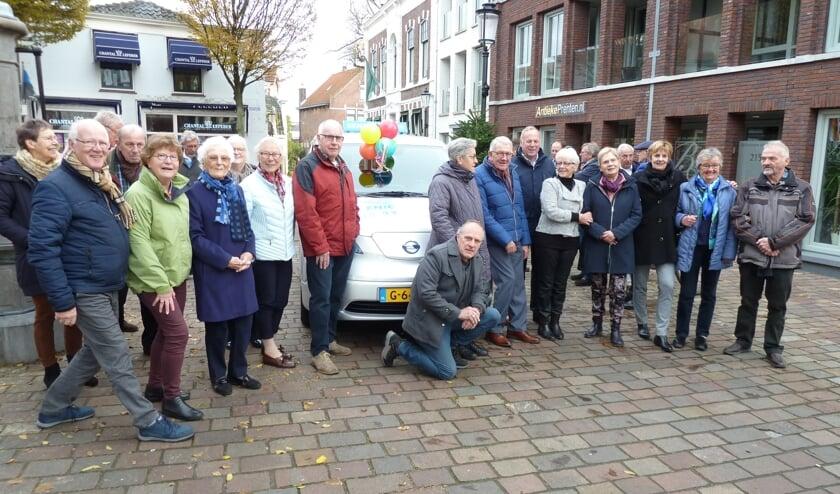 De seniorenbus wordt bijna aan het zicht onttrokken door de groep vrijwilligers.