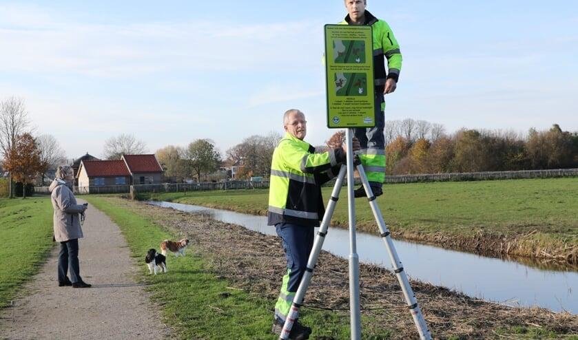 Gemeentemedewerkers Aad Heemskerk (l) en Bas de Zwart plaatsen de borden op Koudenhoorn.| Foto: Novus Image - Esther Moonen