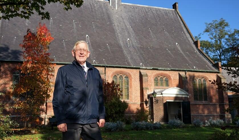 Dick de Boer bij de Dorpskerk, die een belangrijke rol speelt in het boek.   Foto: C. v.d. Laan
