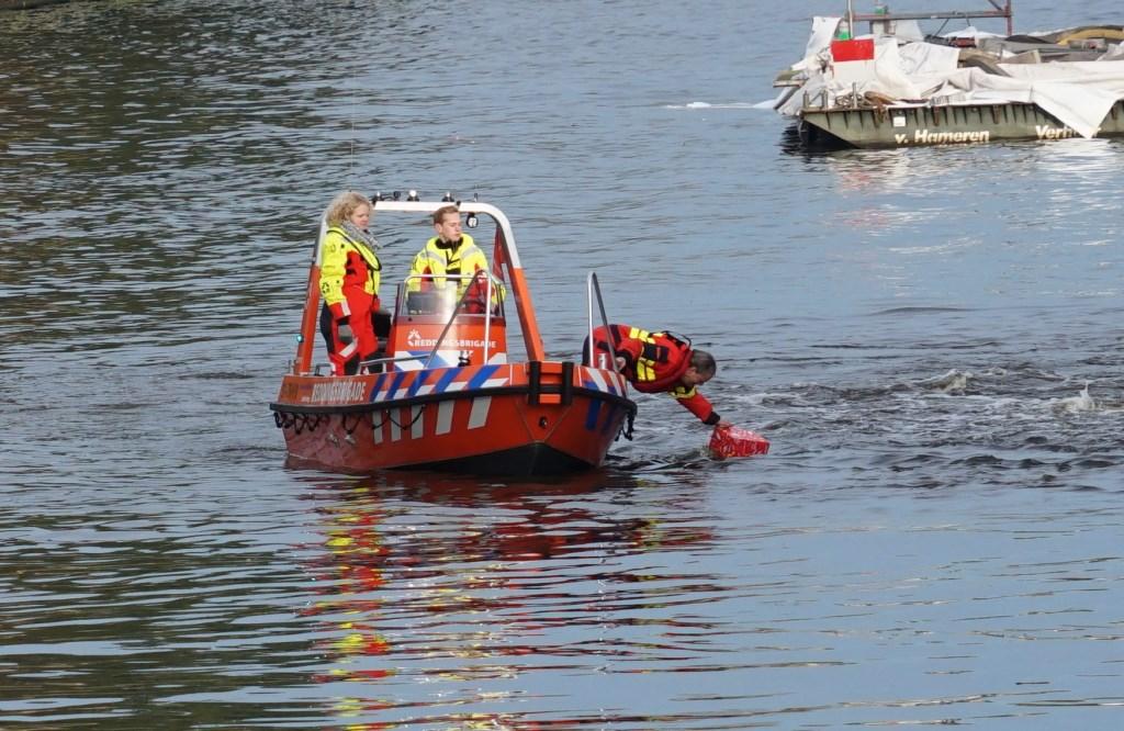 De reddingsbrigade recht een van de pakjesboot gevallen cadeautje.  Foto: Corrie van der Laan © uitgeverij Verhagen