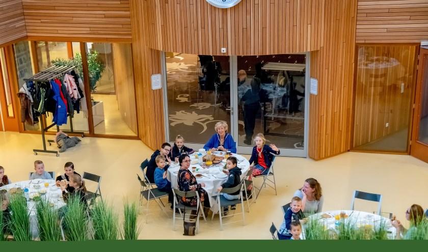 Burgemeester Laila Driessen (achteraan aan de middelste tafel, hapt een gezond en gezellig ontbijtje weg met de kinderen van De Hasselbraam.