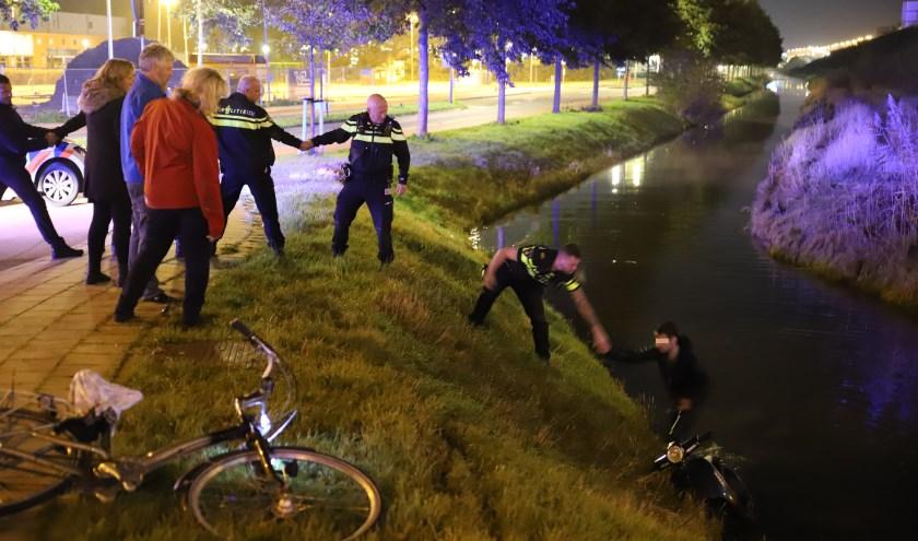 Een politieman helpt de beschonken scooterrijder op de kant.