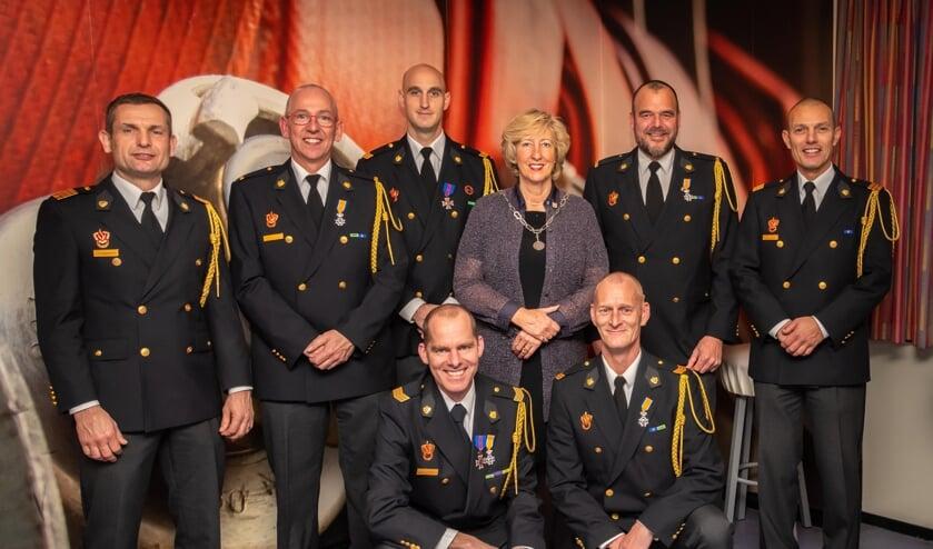 V.l.n.r. staand Tjeerd Neumann (directeur brandweerzorg), Arno Sormani, Michael van Biezen, burgemeester Laila Driessen, Frank Arnoldus en Edo Groenendijk (clustermanager). Op de voorgrond v.l.n.r. Wouter Verbiest en Peter Marsé.