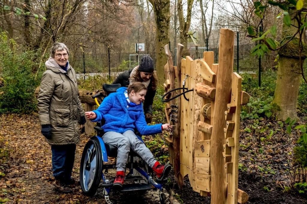 Voorzitter Riny Vons van de Natuurspeeltuin met Anne en Nadja van Swieten bij de beleefmuur.   Foto: J.P. Kranenburg © uitgeverij Verhagen