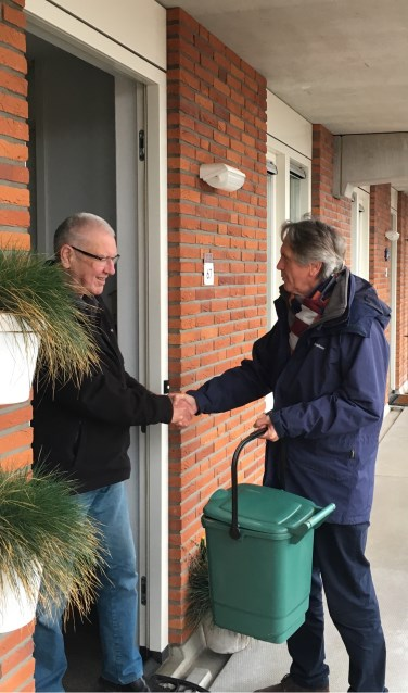 De voorzitter van de VVE neemt het eerste GF-containertje in ontvangst