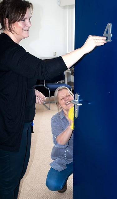Wethouder Angelique Beekhuizen schroeft het kamernummer van een deur die ondertussen schoongemaakt wordt door Bernadette Pollen van Stichting MOL.