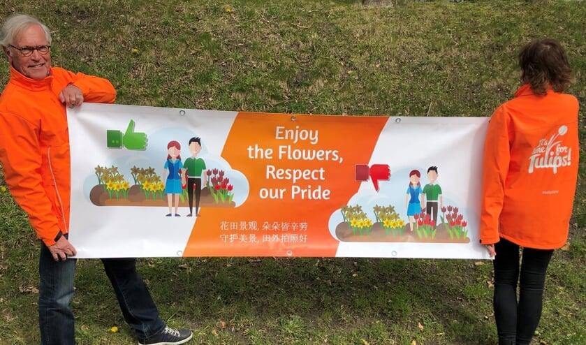 Deze banner vraagt de toeristen om respectvol genieten van de bollenvelden. | Foto: PR