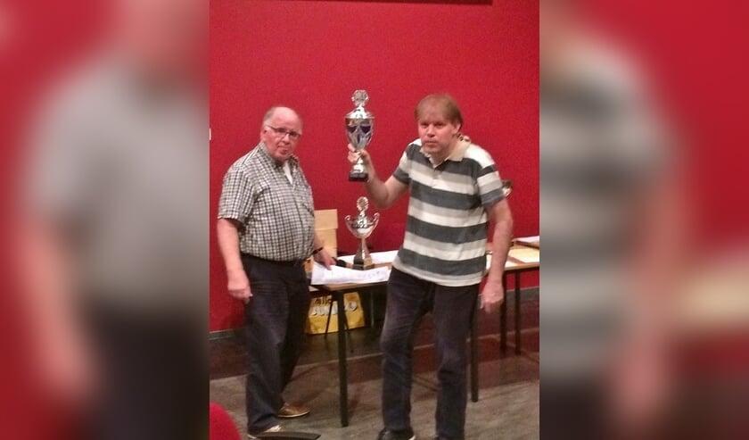 Internationale schaakmeester Fred Slingerland neemt uit handen van wedstrijdleider Cok Ippel de beker in ontvangst.