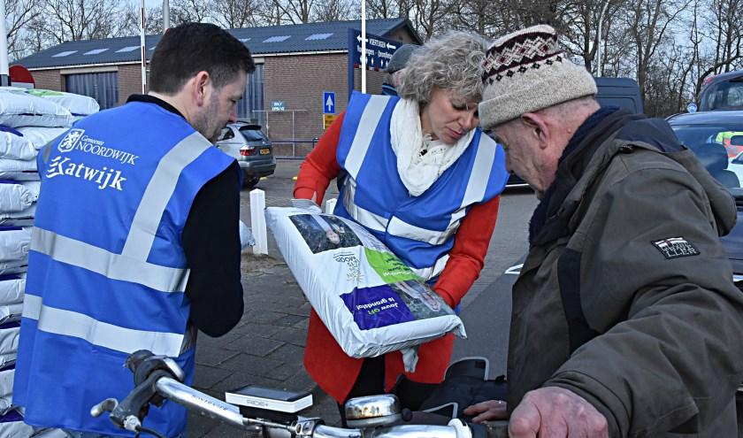 De wethouders Van Starkenburg en Salman deelden zakken compost uit.   Foto: Piet van Kampen
