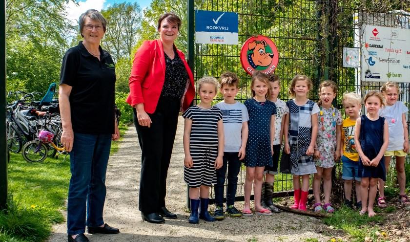Wethouder Angelique Beekhuizen (met rood jasje) heeft, onder toeziend oog van een groep speeltuingebruikertjes, het bord 'Rookvrij' onthuld. Links voorzitter Riny Vons van de Stichting Natuurspeeltuin Leiderdorp.