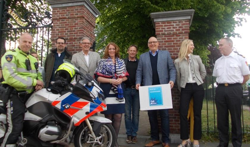 De tweede tegel van het Keurmerk Veilig Ondernemen in Sassenheim. Carla Breuer, John van der Tol, politie, brandweer, ondernemers en ambtenaren kijken toe. | Tekst en foto: Piet de Boer