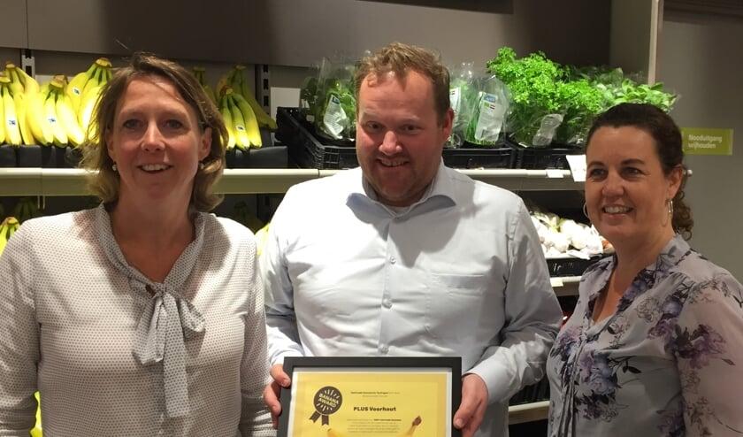 Miranda van Leeuwen en Wendela Seyger van Ladies' Circle Voorhout, ambassadeur van Teylingen Fairtrade Gemeente, overhandigen de Banana Award aan eigenaar Joop van Dijk. | Foto: pr.