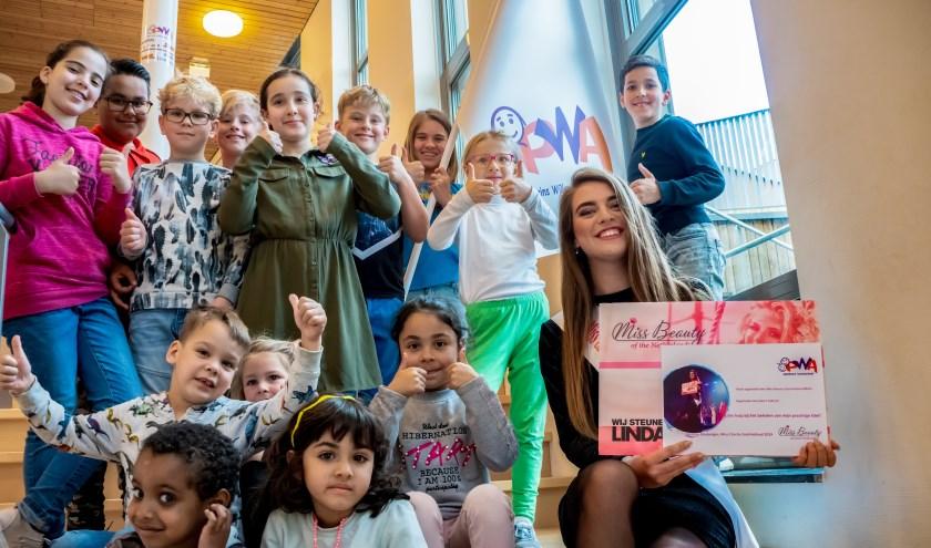 Whitley Glasbergen met een aantal leerlingen van de PWA die haar hebben geholpen geld in te zamelen voor de LINDA-foundation. | Foto: J.P. Kranenburg