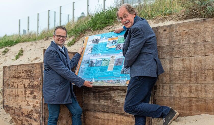 Wethouder Jacco Knape (links) en voorzitter Jack VlielandDUNAatelier plaatsen het informatiebord.
