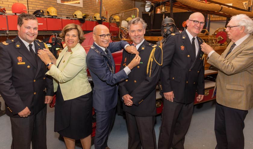 Burgemeester Emile Jaensch en oud-burgemeesters Els Timmers-Van Klink en Sjoerd Scheenstra speldden de draagspeldjes op bij de brandweerlieden.