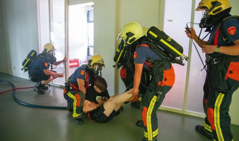 De brandweer brengt een slachtoffer van de rook in veiligheid.