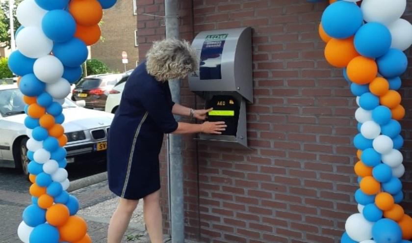 Wethouder Corien van Starkenburg hangt een AED op aan het gemeentehuis