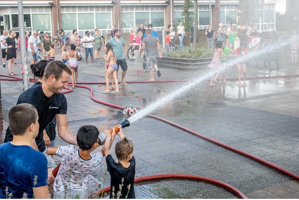 Met hulp van de brandweermensen mochten kinderen zelf ook spuiten met een brandweerslang.    Foto: J.P.Kranenburg © uitgeverij Verhagen