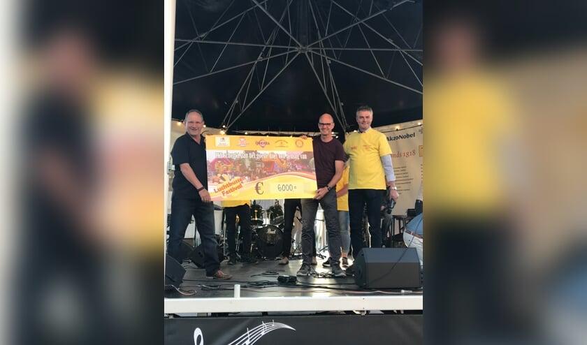 Erik van der Veld, Claus van der Zalm (bestuurslid Voorhoutse IJsclub) en Ruud Neuteboom poseren met de cheque.