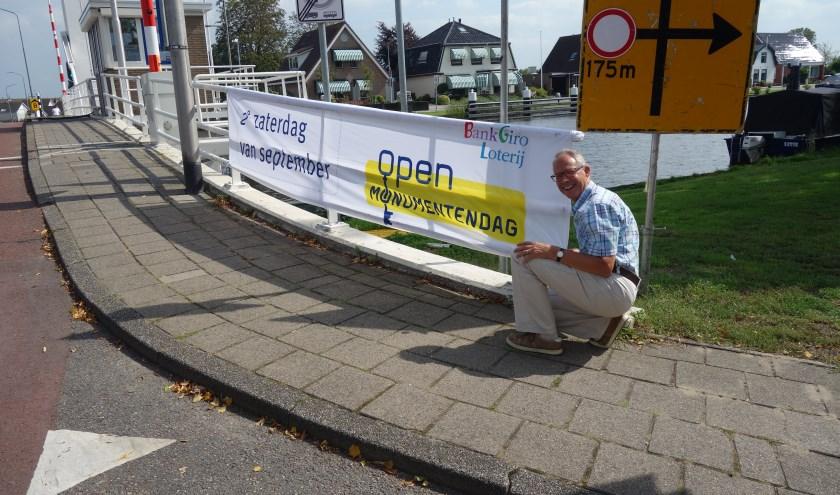 """Eric Prince, voorzitter """"Oud Lisse"""" en van het Comité Open Monumentendag Lisse, knoopt eigenhandig het spandoek aan de brug."""