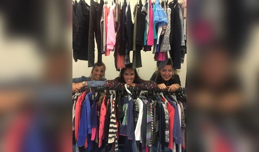 Marina, Ramona en Monique organiseren de kledingbeurs.