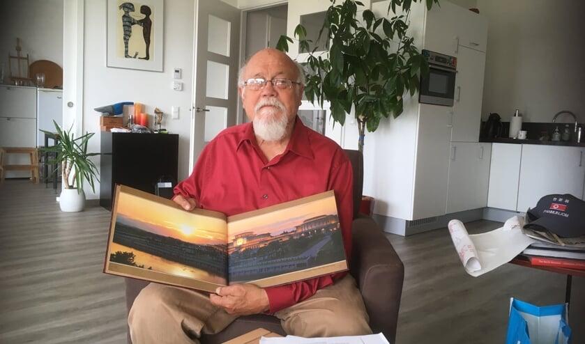 Boll Thomson thuis met een fotoboek over Noord-Korea. | Foto: CvdS