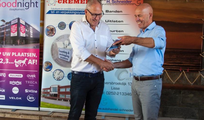 Tom Rooijakkers (rechts) overhandigt het eerste boekje aan oud-pikeur Bert van Dooyeweerd. | Foto: pr