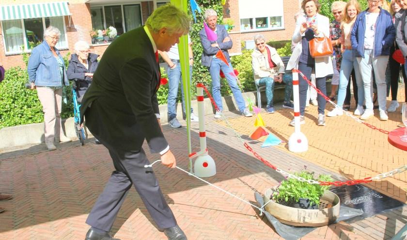 Wethouder Kees van der Zwet onthult de buurtprijs in de vorm van een tegel.