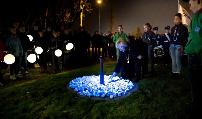 Burgemeester Laila Driessen legt een steen op het Levenslicht herdenkingsmonument.