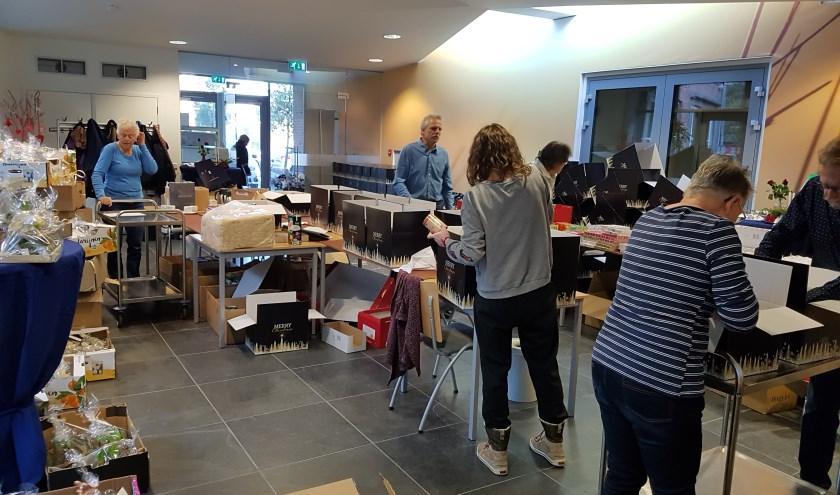 Vrijwilligers werken hard om alle kerstpakketten klaar te maken.   Foto: PR