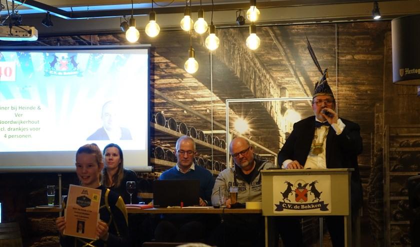 Voorzitter Theo van Werkhoven, voor de gelegenheid ook veilingmeester, veilt een van de 200 kavels.