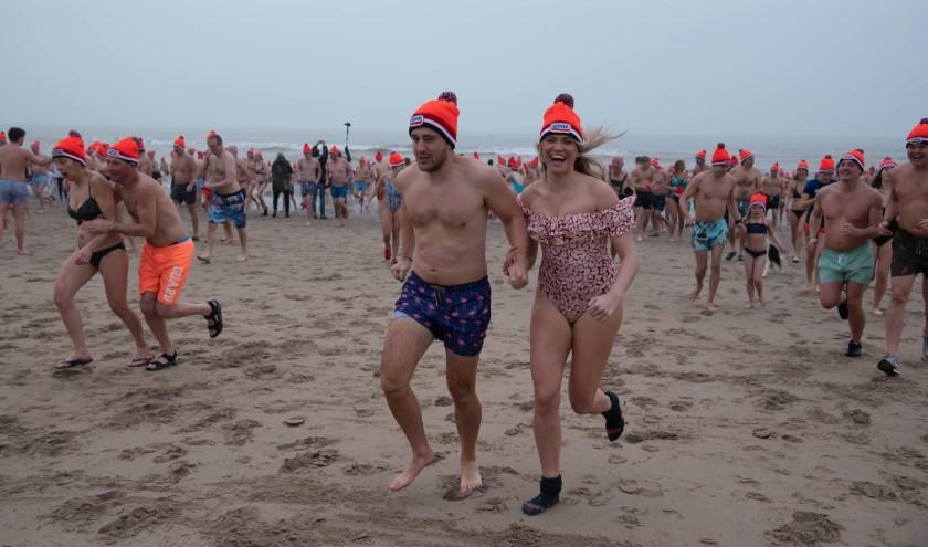 Lachend uit de koude zee rennen: zouden het de sokken zijn? Deze dame heeft er ondanks de kou nog zichtbaar lol in. | Foto: Richard van Egmond.
