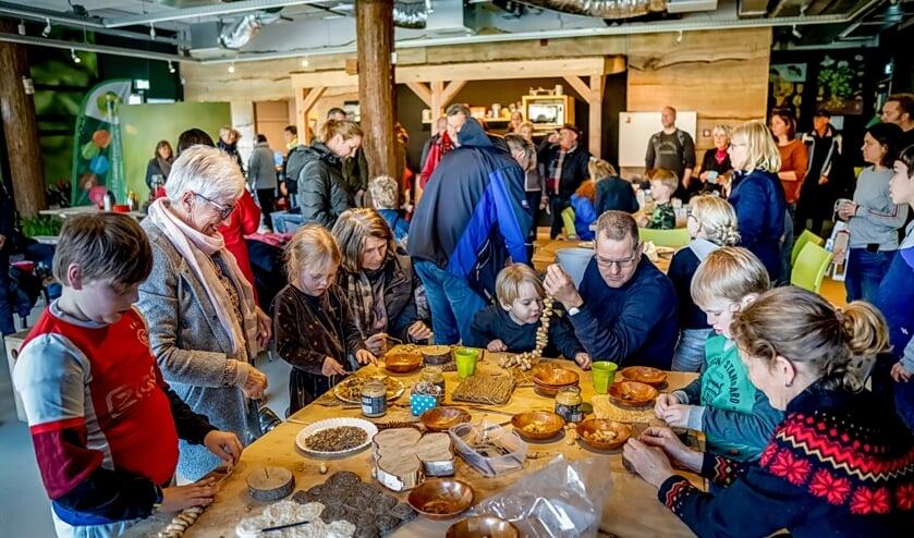 Jong en ouder werken ijverig aan het maken van pindaslingers. | Foto: J.P. Kranenburg
