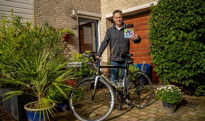 Hans van Hartevelt met de fiets waarop hij vele kilometers aflegt en zijn nieuwste boek. | Foto: J.P. Kranenburg